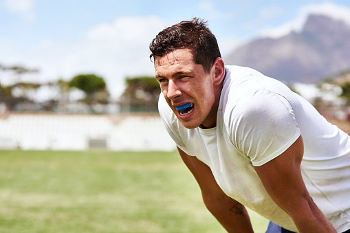 Man wearing a mouthguard leaning forward
