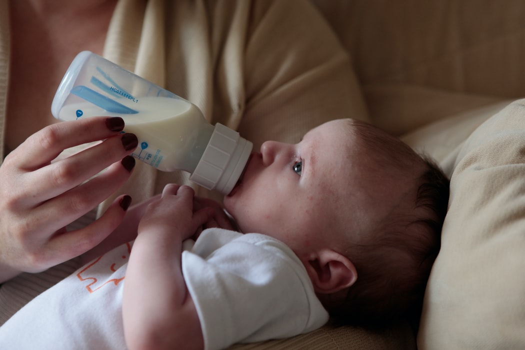 Baby held in a woman's arm being fed formula