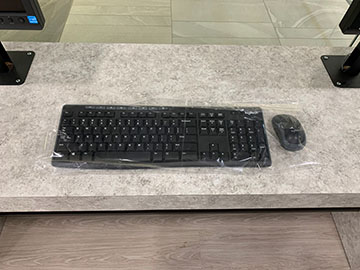 Computer keyboard and mouse covered in clear plastic