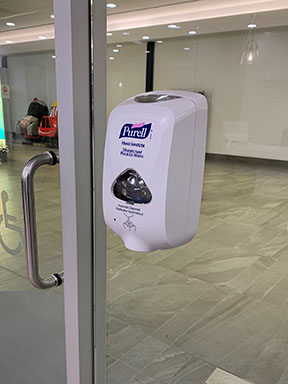 Hand sanitizer on glass wall at entrance of the clnic