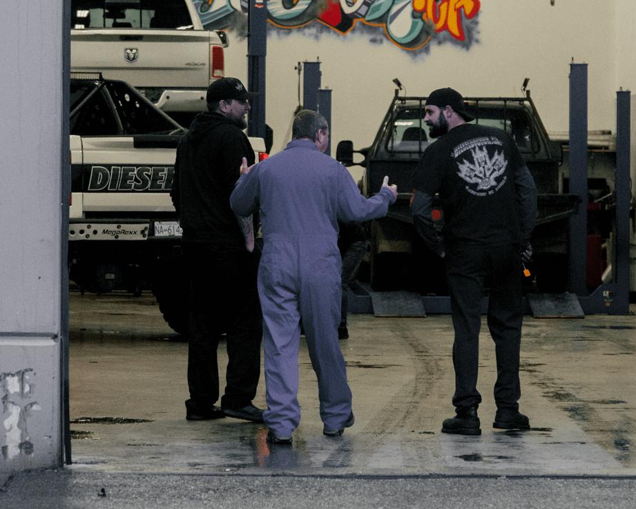 Diesel repair shop owners walking a customer through the shop