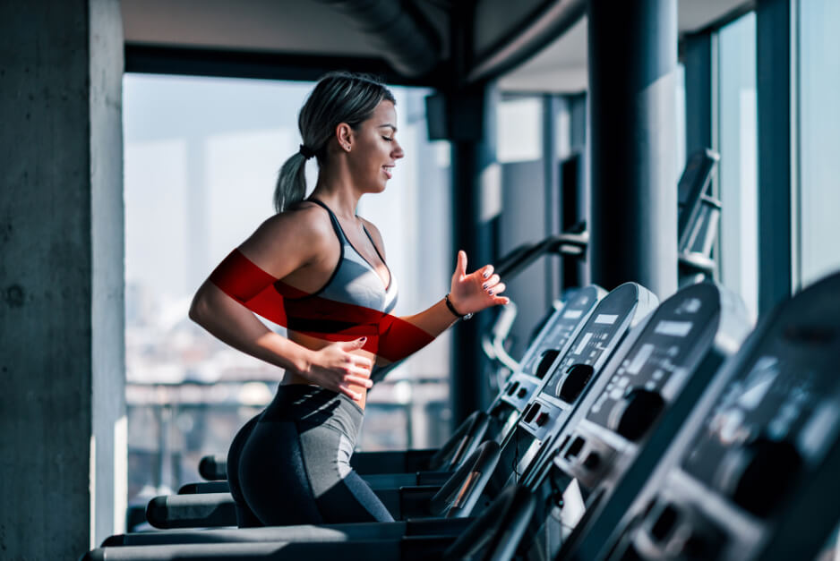 Woman running on a treadmill inside a gym