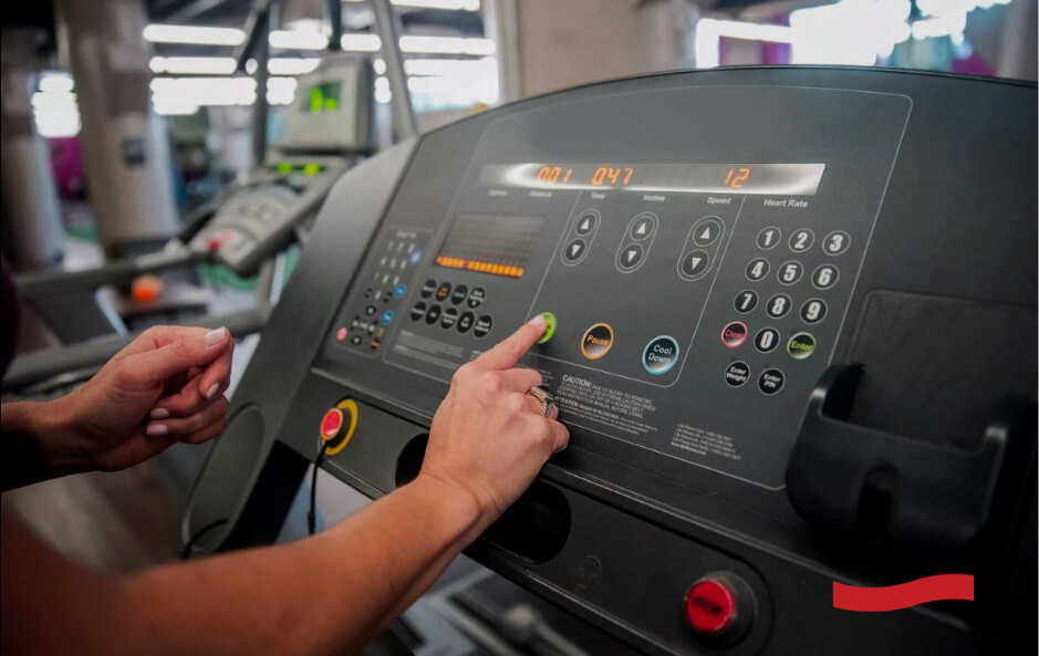 Photo of a woman's hand pressing a control button on a treadmill
