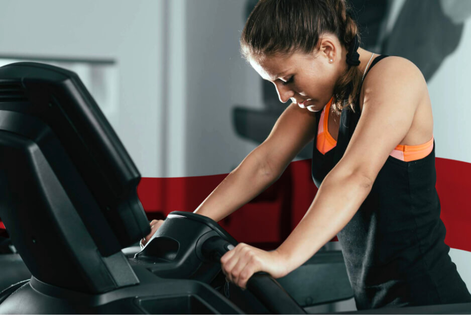 Woman wearing black tank top holding on to treadmill handrails