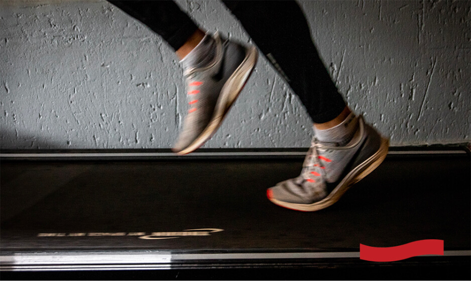 Photo of a runner's gray and orange shoes while running on a treadmill