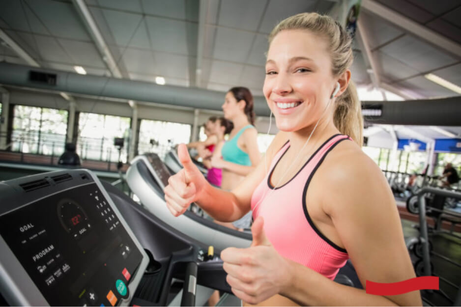 Close up photo of a blonde haired woman smiling and giving a thumbs up sign while running on a treadmill