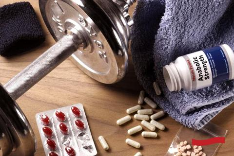 Photo of dumbbell, blue towel, different capsules and tables and prescription bottle on wood flooring.