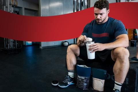 Man sitting inside a gym preparing a protein shake