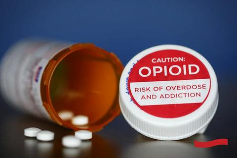 Small, white tablets spilled out of an orange prescription bottle with a white cap cover printed with OPIOID warning