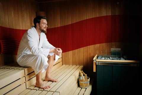 Man in white robe sitting inside an infrared sauna