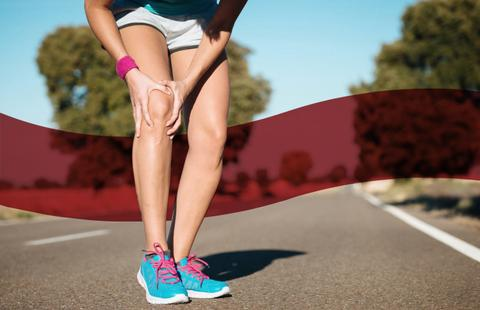 Close up shot of a runner wearing pink and blue shoes, while holding her knee in pain