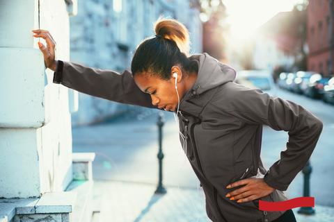 Photo of a tired looking female runner wearing a gray hoodie, leaning on a wall for support