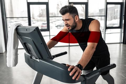 Photo of an exhausted looking man holding onto a treadmill