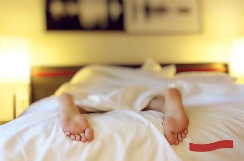 Photo of someone's feet peeking out from under bed covers while sleeping