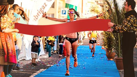 Photo of a female marathon runner going through the finish line