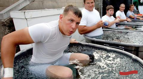 Photo of 5 male athletes wearing white shirts soaking in tubs full of ice