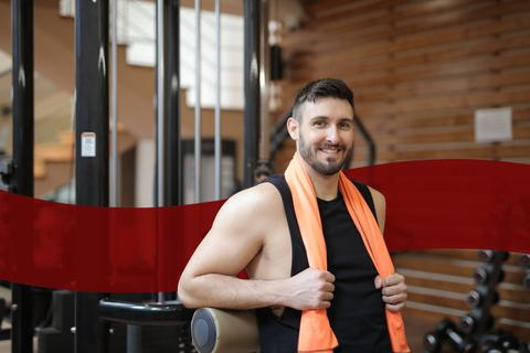 man wearing balck shirt holding orange towel inside a gym