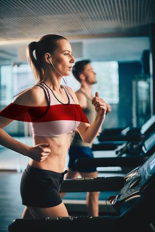 woman wearing sports bra running on a treadmill