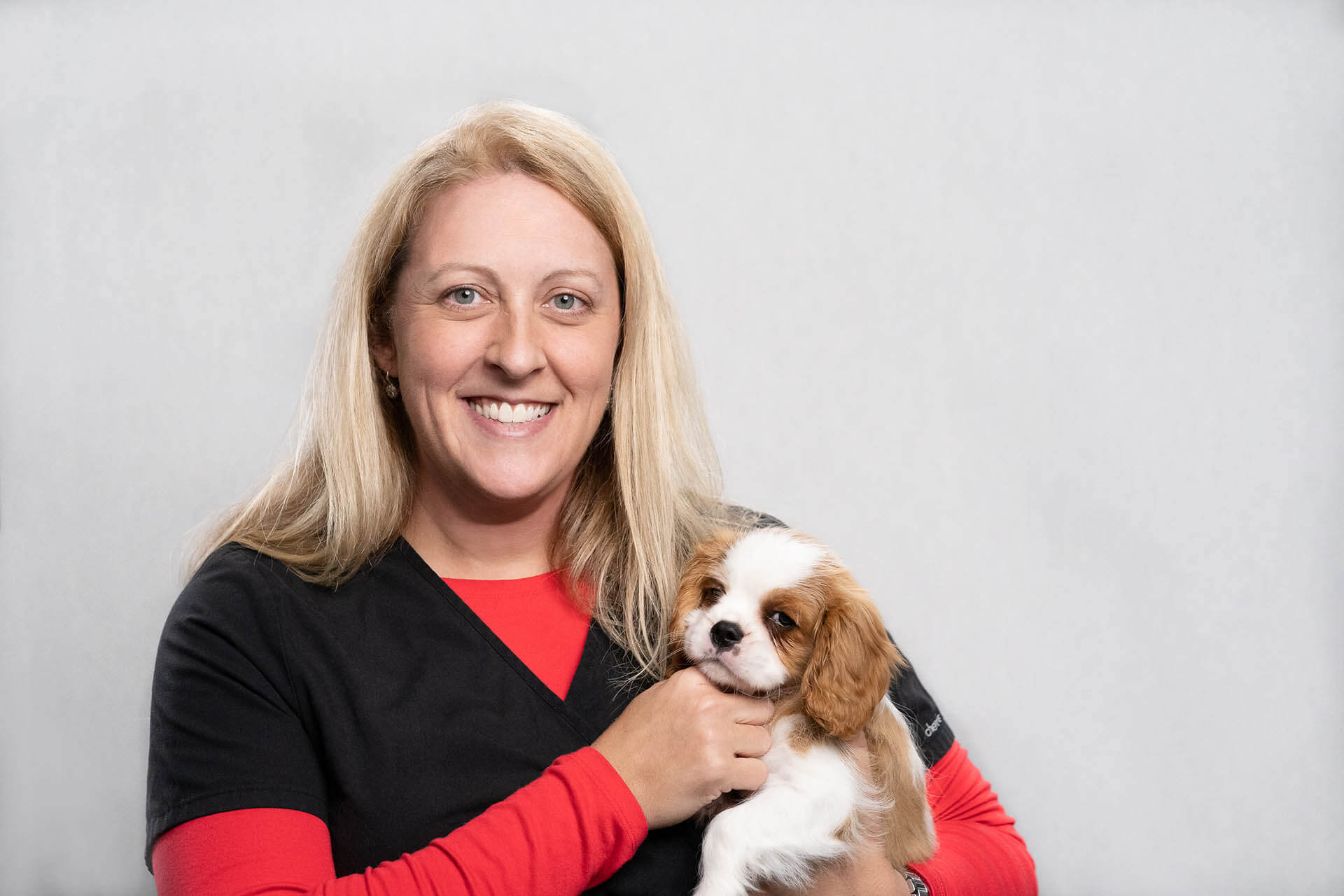 This is a picture of an employee of Mobile Pet Vax holding a puppy
