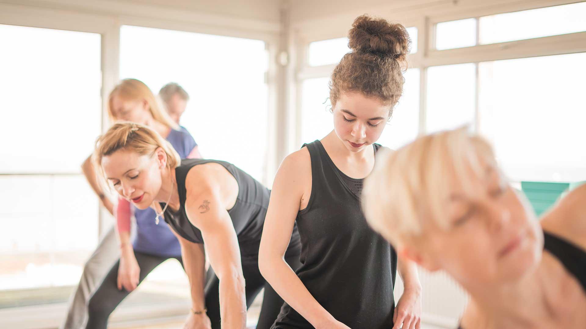 Young women practising pilates in a studio.