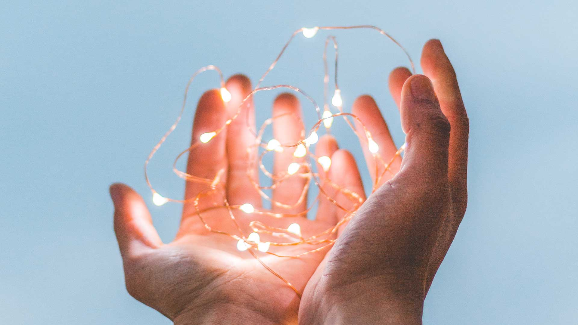 photo of hands holding fairy lights