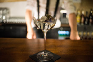Dry martini on bar with edible flower garnish