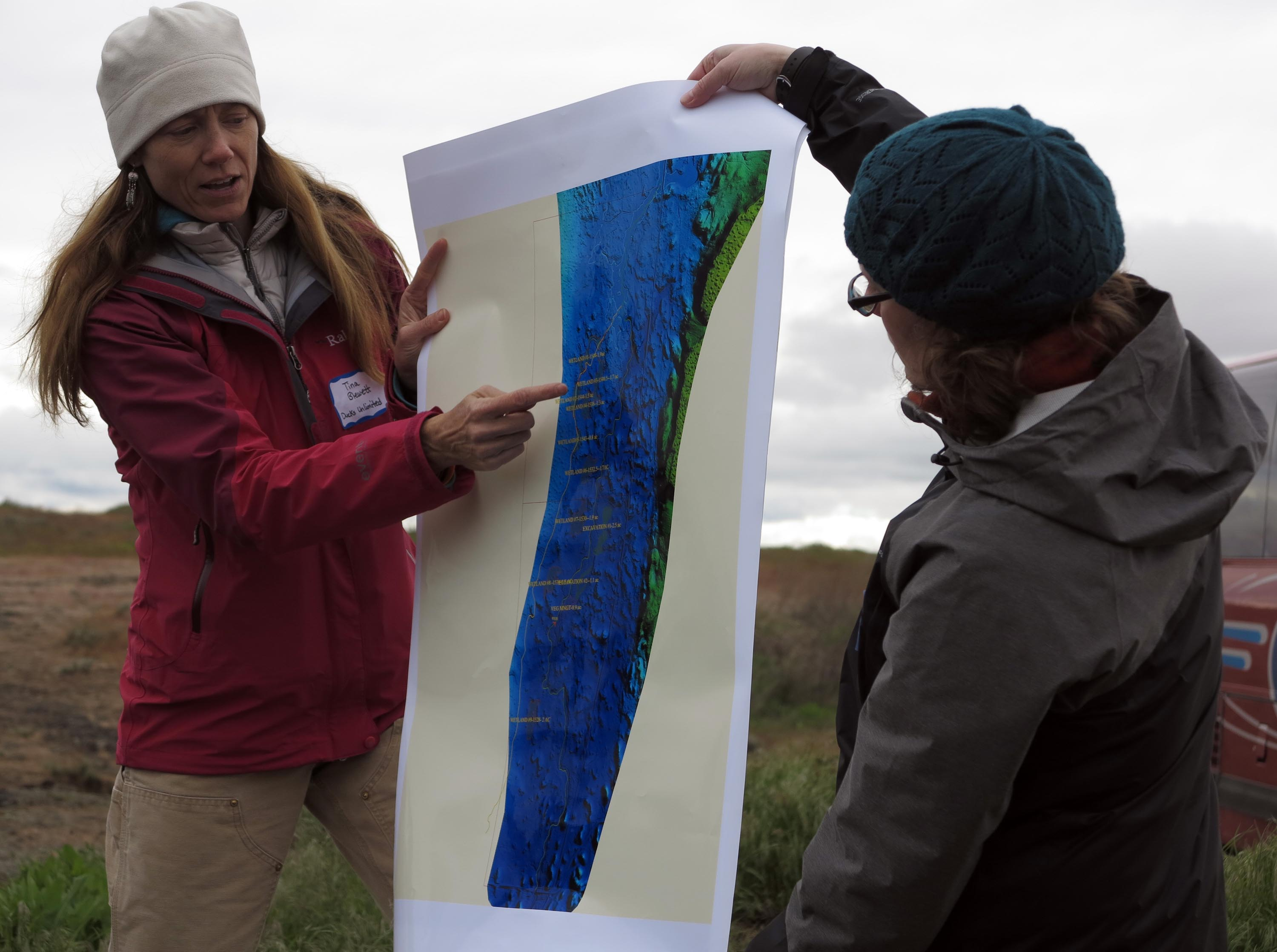 Two people holding large printed page with LIDAR Data visuals