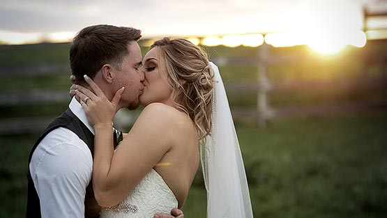 Husband and wife kissing in front of the sunset on a ranch