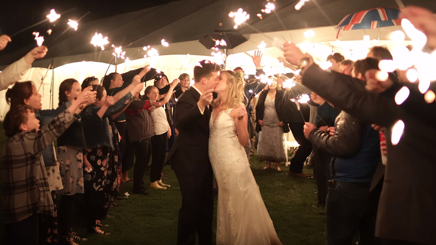 Husband and wife kissing surrounded by family holding sparklers