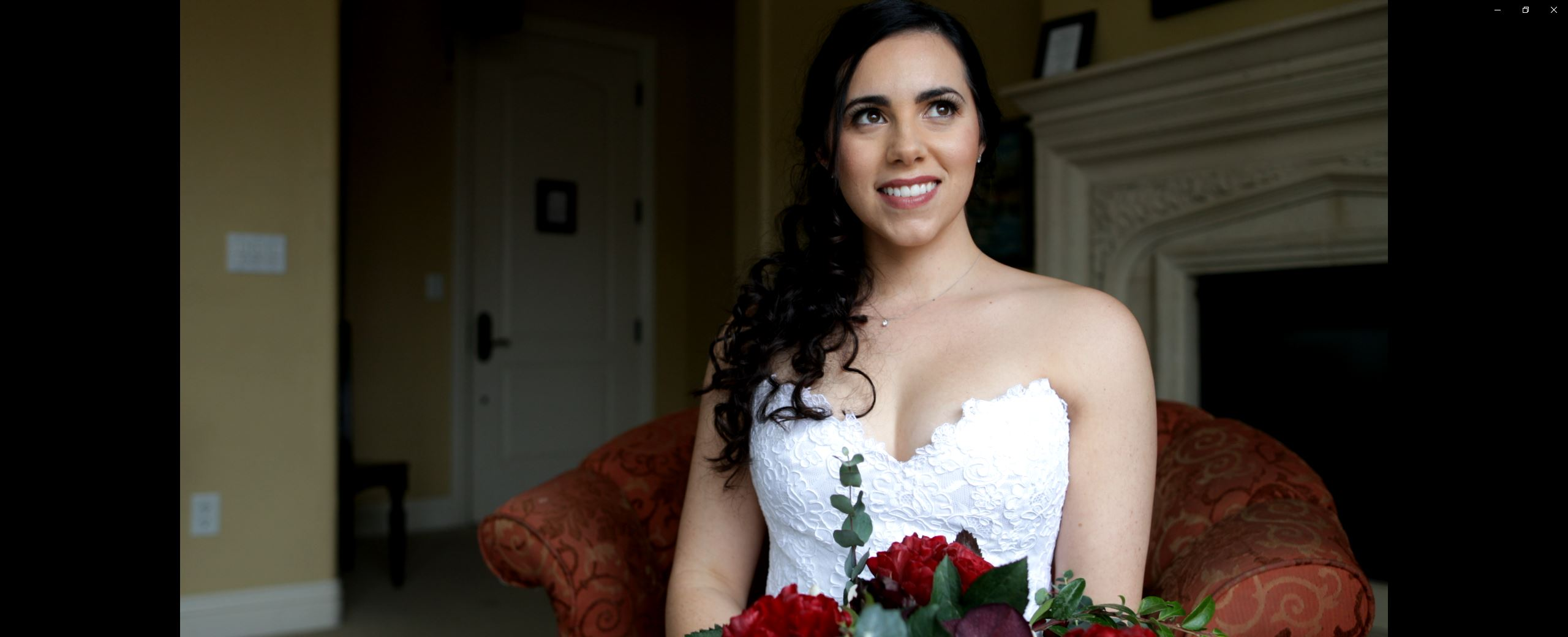 Bride sitting in a chair in hotel room smiling with flowers in Sacramento, ca