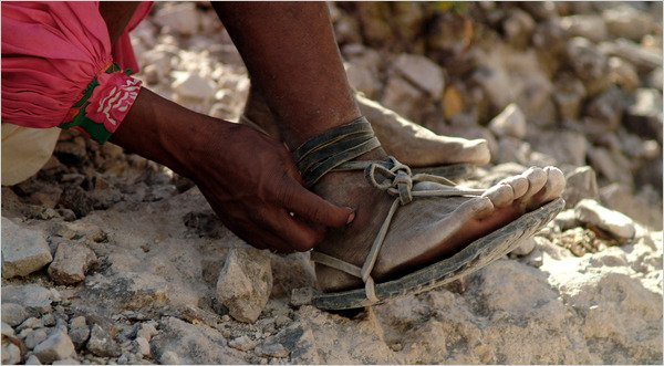 BASIC FOOTWEAR Arnulfo Quimare, a Tarahumara Indian who is a champion distance runner, laces up his sandals for a 50-mile race on canyon trails.  Credit Luis Escobar