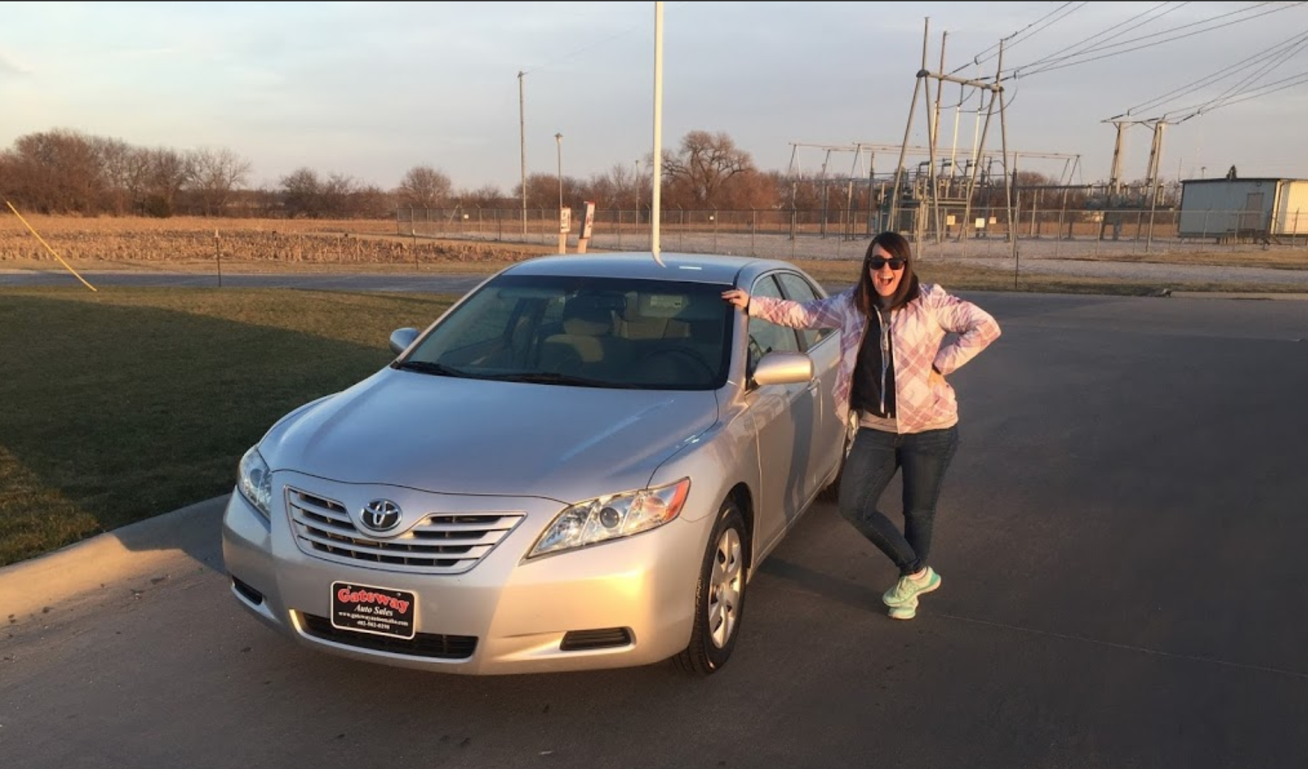 A photo of a happy customer with her car being sold