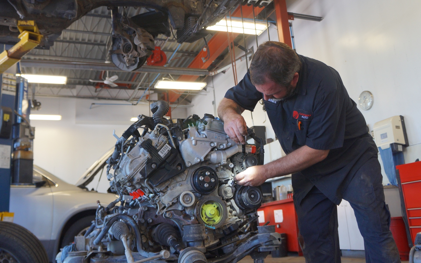 One of Gateway Auto's mechanical technicians working on an engine