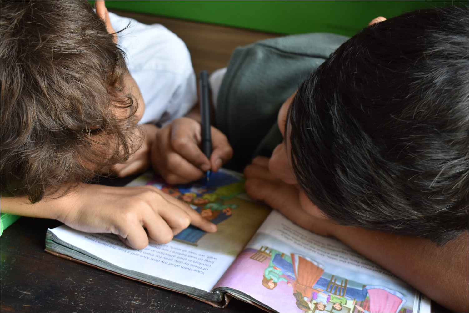 two little boys reading a book together