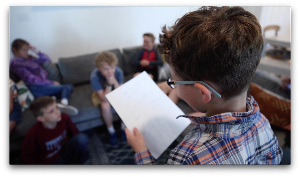little boy wearing glasses reading a paper to the class