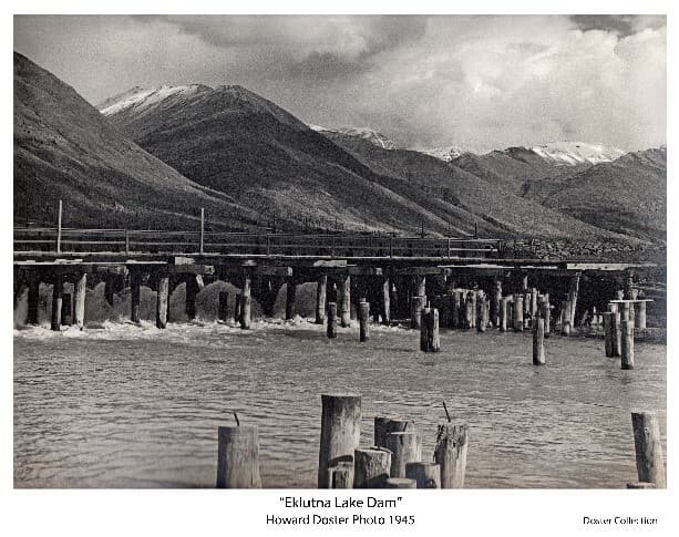 Image shows the lower side of Eklutna Lake Dam spillway with numerous wooden pilings standing in water in the foreground and mountains beyond. Water flowing through the spillway is evident providing the standing water in foreground. Head gate controls on the spillway are evident and numerous pilings exhibit metal bars protruding from their tops. Early season snow is evident on mountain tops.