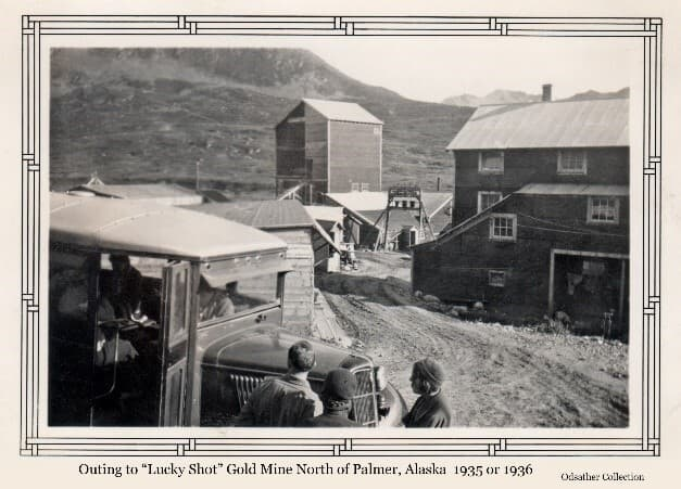 """Image shows a collection of large buildings in a summer alpine setting, identified as the """"Lucky Shot"""" Gold Mine, with mountains in background. An ARRC bus is in foreground with people standing in front and others visible inside."""