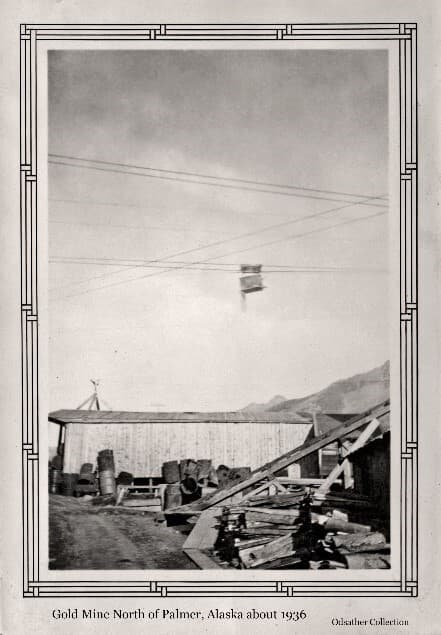 """Image shows a building in a summer setting, identified as part of the """"Lucky Shot"""" Gold Mine, with a large collection of steel barrels and lumber in the foreground, wires and an aerial tram car overhead, and mountains in background."""