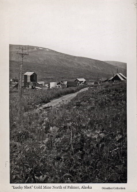 """Image shows a collection of buildings in an alpine setting, identified as the """"Lucky Shot"""" Gold Mine, with power poles, electric lines, and a roadway in the foreground. Alpine vegetation is visible in foreground and rounded mountains in background."""