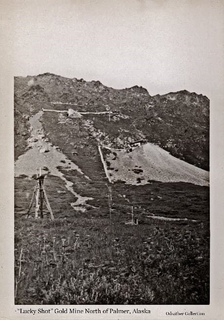 """Image shows a rugged mountainside with large tailing piles spilling down and buildings, covered stairways and tramways adjacent. Identified as the """"Lucky Shot"""" Gold Mine, (Upper Lucky Shot above and Lower Lucky Shot below). A wooden tower and power poles are visible, and alpine vegetation is in foreground."""