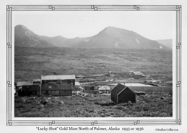 """Image shows a collection of buildings in a summer alpine setting, identified as the """"Lucky Shot"""" Gold Mine, with mountains in background."""