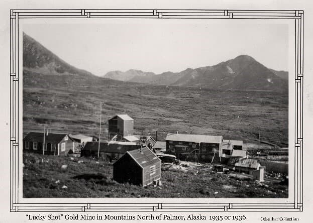 """Image shows a collection of buildings in an alpine setting, identified as the """"Lucky Shot"""" Gold Mine, with mountains in background. A bus (probably an ARRC bus) and an automobile are visible near the buildings."""