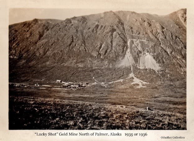 """Image shows an alpine valley a with a rugged mountainside and large tailing piles spilling down its side. Buildings are visible above the tailings and in the valley below. Identified as the """"Lucky Shot"""" Gold Mine, (Upper Lucky Shot above and Lower Lucky Shot below). Alpine vegetation is in foreground."""