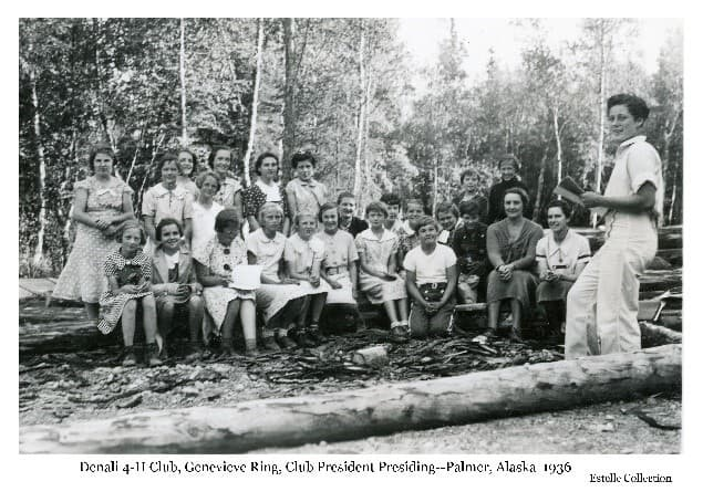 Image shows a group of young girls and two women seated on logs in a wooden setting. One girl, identified as Genevieve Ring, is standing and appears to be leading the group in some activity. Two women are seated with the group, identified as Ruth Peck on the left and Ruth DeArmond on the right of the photo.