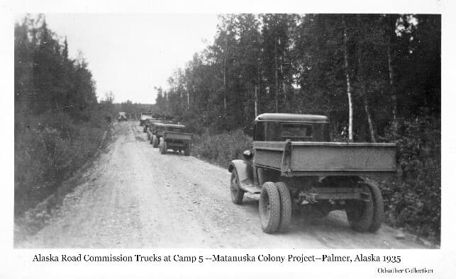 """Image shows a group of Alaska Road Commission dump trucks on what was then called the """"Werner Cut-off"""" road (now the Palmer-Fishhook Road). Location is at Colonist Camp #5 per notes on a similar photo in the Nichols Collection."""