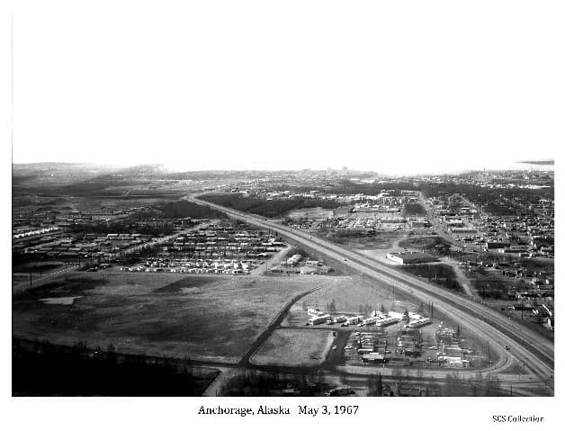 Image shows an oblique view of Anchorage looking west from above the Pine Street intersection with the Glenn Highway.