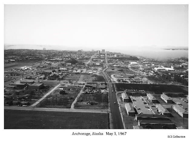Image shows an oblique view of Anchorage looking west from above 3rd Avenue at about the intersection with Reeve Boulevard.