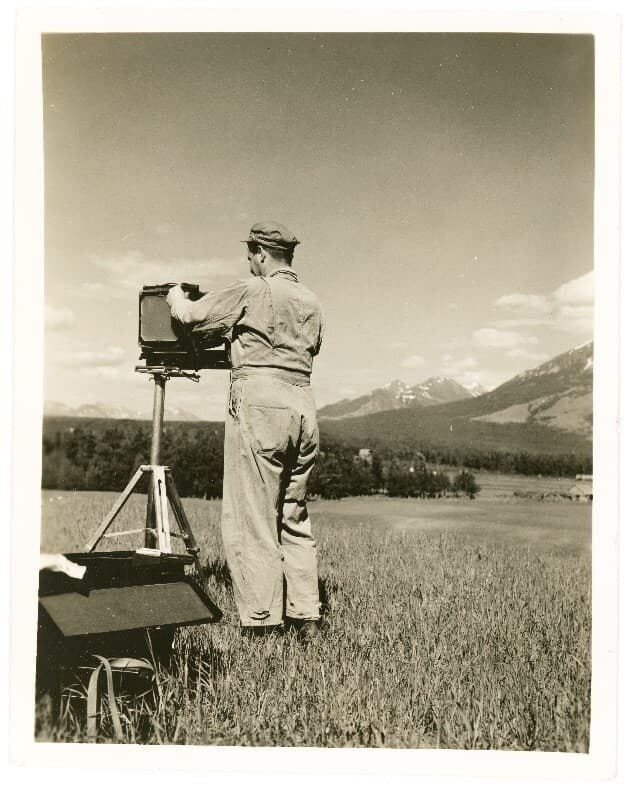 Image is of an army photographer setting up his view camera. Location is atop homesteader John Bugge's hill with fields and forest land in foreground and middle ground. Mountains beyond. Camera is oriented for photographing the town of Palmer. This photo was probably taken the same day as the one coded Man@1-Plt in the Plitt collection.
