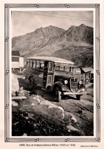 Image shows an ARRC Bus parked with open door at the Independence Gold Mine, partial buildings are visible behind the bus. Mountains are in background.