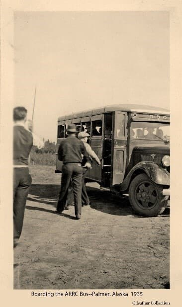 Image shows men approaching an ARRC bus. The bus door is open, driver and other riders are visible inside. A tent is partially visible beyond.  Since private vehicles were scarce in early days of the colony, the Corporation busses offered a way for people to travel between camps and home sites as they, and the roads, developed.